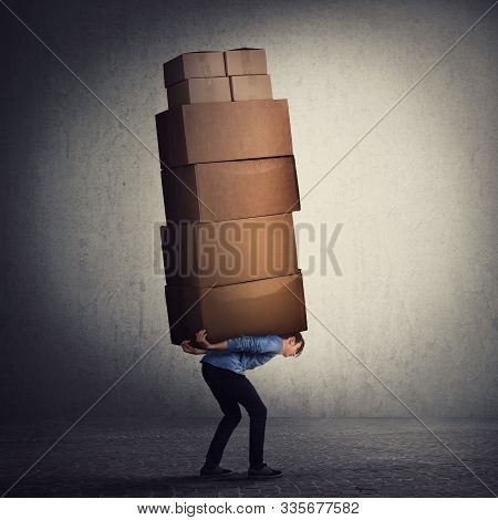 Bent down guy carrying a lot of big heavy boxes on his back. Overloaded of daily tasks, and difficult burden. Packing stuff and moving concept. Mail worker package delivery before christmas holidays. stock photo