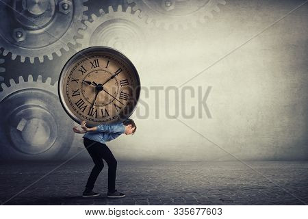 Bent down guy carrying a big heavy clock on his back. Overloaded student tired of daily tasks, and difficult burden. Time pressure and management concept, schedule efficiency, planning and control. stock photo