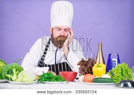 Culinary inspiration. Hard day at restaurant. Tired and exhausted chef. Man bearded chef cooking food. Chef fed up of boring meals. Looking for inspiration. Bored chef lean on table at kitchen stock photo