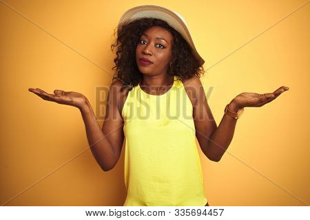Young african american woman wearing t-shirt and hat over isolated yellow background clueless and confused expression with arms and hands raised. Doubt concept. stock photo
