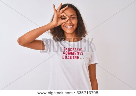 Brazilian woman wearing fanny t-shirt with irony comments over isolated white background with happy face smiling doing ok sign with hand on eye looking through fingers stock photo