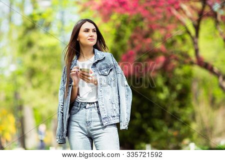Smiling caucasian brunette young woman sending message on smartphone outside alone Wear jeans clothes .Technologies and gadgets. Advertising for shop selling electricity and mobile phones. stock photo
