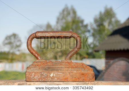 Old rusty Vintage iron with big corroded handle for ironing. Antique household item on sunny day stock photo