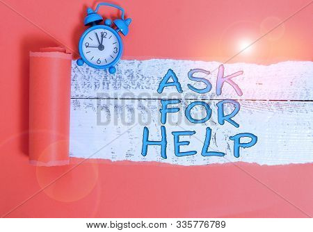 Handwriting text writing Ask For Help. Concept meaning Request to support assistance needed Professional advice Alarm clock and torn cardboard placed above a wooden classic table backdrop. stock photo