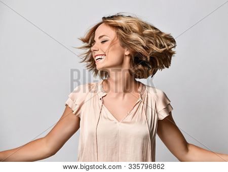 young woman in a beige short-sleeved satin blouse shakes her head with her hair. The concept of joy, happiness, joy, fun stock photo