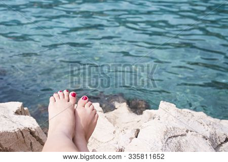 Vacation Concept. Tanning on the Beach. Woman's Bare Feet over Sea background.Beautiful bare feet on a background of the sea. stock photo