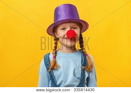 Funny child clown, hat and a red nose. Cheerful little girl on a yellow background. April 1. April Fools Day. Copy space. stock photo