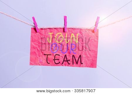 Handwriting text writing Join Our Team. Concept meaning Allied Associate Work with us New Employee Hired Enlist Clothesline clothespin rectangle shaped paper reminder white wood desk. stock photo