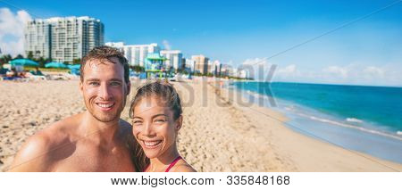 Miami beach happy couple taking selfie on USA Florida on summer travel winter vacation. Interracial people smiling on south beach. Biracial Asian girl, young man banner panorama. stock photo