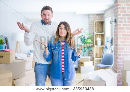 Young beautiful couple standing at new home around cardboard boxes clueless and confused expression with arms and hands raised. Doubt concept. stock photo