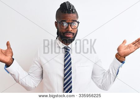 African american businessman with braids wearing tie glasses over isolated white background clueless and confused expression with arms and hands raised. Doubt concept. stock photo