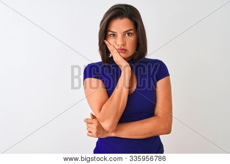 Young beautiful woman wearing blue elegant t-shirt standing over isolated white background thinking looking tired and bored with depression problems with crossed arms. stock photo