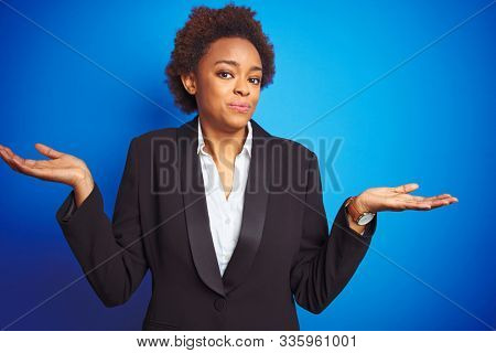 African american business executive woman over isolated blue background clueless and confused expression with arms and hands raised. Doubt concept. stock photo