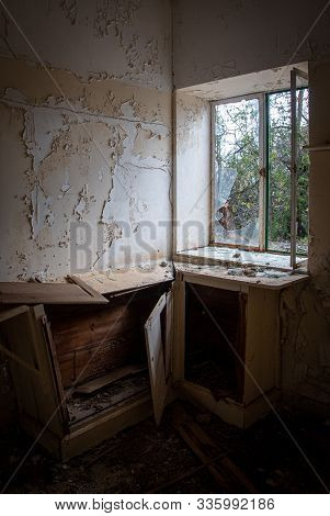 Interior Of A Dirty An Empty Demolished Abandoned Cuisine Room With Broken Furniture, Open Door An D
