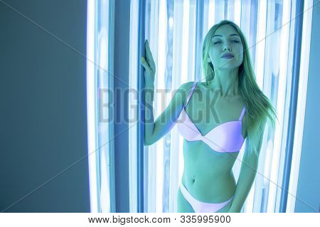 Beautiful slender blonde sunbathes in the solarium. A girl in a vertical tanning bed stands and smiles. Tanning studio. spa. stock photo