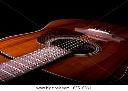 A closeup photo of an acoustic guitar featuring its body, fretboard and soundhole. stock photo