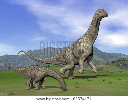 Mother argentinosaurus dinosaur and baby eating in green landscape by day stock photo