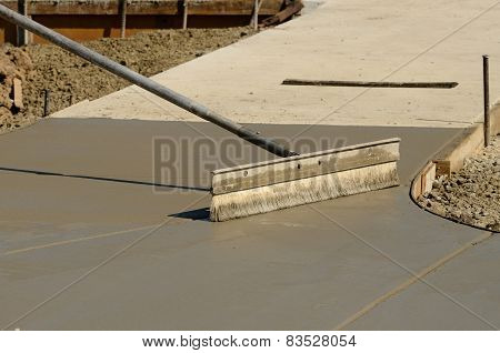 Concrete mason contractor using finishing broom to texture a new sidewalk at a new commercial residential development project stock photo