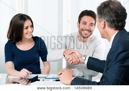 Happy couple seal a deal with their personal financial advisor at home stock photo
