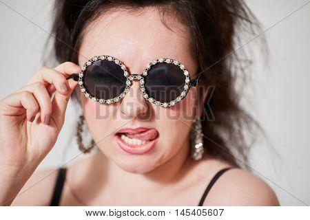Dark-haired girl model in stylish round dark glasses shows tongue posing in studio. stock photo