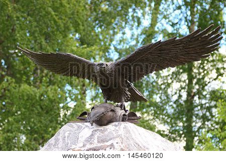 A bronze eagle taking off a stone monument with cuirass of a dead soldier. Russia Borodino. stock photo