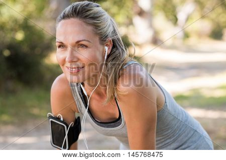 Portrait of athletic mature woman resting after jogging. Beautiful senior blonde woman running at th