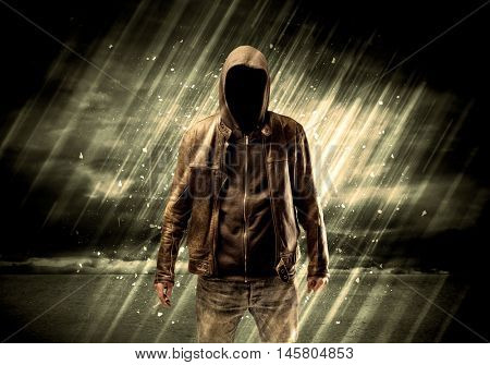 An incognito hooded stalker standing in the rain with his back in front of dark scary landscape concept stock photo