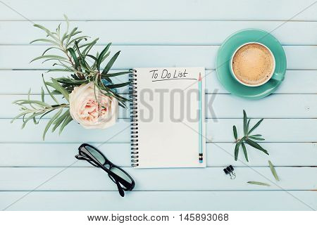 Morning coffee cup, notebook with to do list, pencil, eyeglasses and vintage rose flower in vase on blue rustic table from above. Planning and design concept. Cozy breakfast. Flat lay styling.