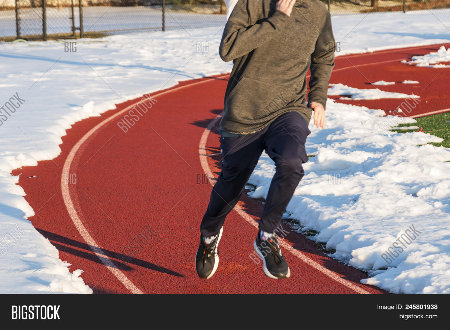 A high school boy is running on a track in lane one with the rest of the track covered with snow during winter track and field practice.