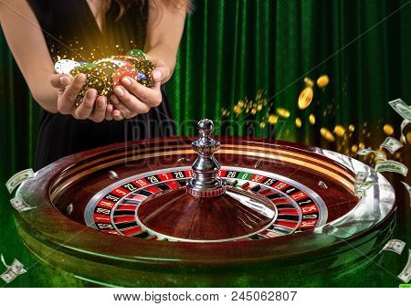 Collage of casino images with a close-up vibrant image of multicolored casino roulette table with poker chips in woman hands. Green background with golden sparks stock photo