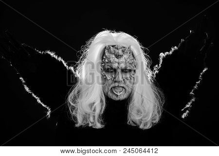 Magic and mystery concept. Dragon with white eyes and sharp thorns on face. Man with black bird wings. Wizard with long silver hair on dark background. Demon with raven or crow feathers. stock photo