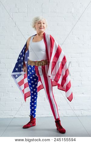 proud senior sportswoman posing with american flag and smiling at camera stock photo