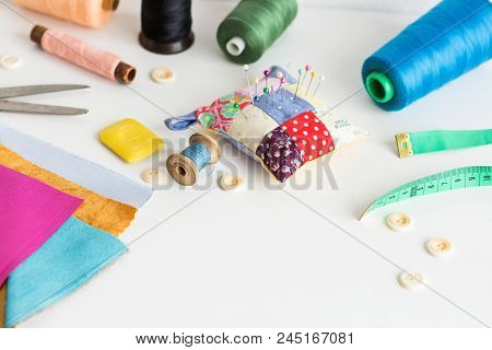 sewing tools close-up, patchwork, tailoring and fashion concept - working environment on a white table, thread spools, buttons, meter, pincushion, scissors, pieces of colorful patchwork fabric, soap stock photo