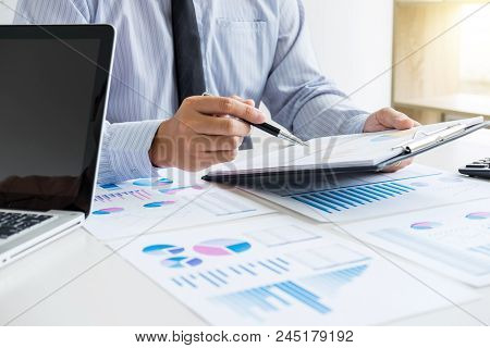 Business man or accountant working Financial investment on calculator with calculate Analyze business and market growth on financial document data graph and writing ,Accounting,Economic,commercial. stock photo