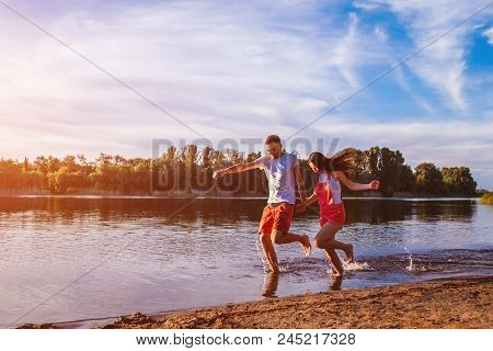 Young man and woman running on summer river bank. Happy c ouple in love having fun at sunset. Guys chilling and enjoying freedom stock photo