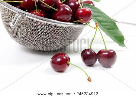 Close up view of white cup with red currant berry isolated on white background. A white cup with red currant berry and small bunch of red currant with small green leaf of currant bush in front of cup. stock photo
