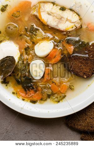 Fish soup with vegetables, rice, herbs and small eggs in white plate. Fresh fish soup with ingredients and spices with bread. Grey background stock photo