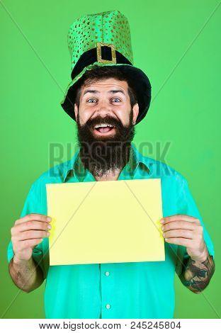 Bearded man in green hat holds yellow board. Bearded man in green men hats celebrate Patrick's Day. Man dressed in carnival headgear Saint Patricks. Saint Patrick's Day. Ireland traditional. stock photo