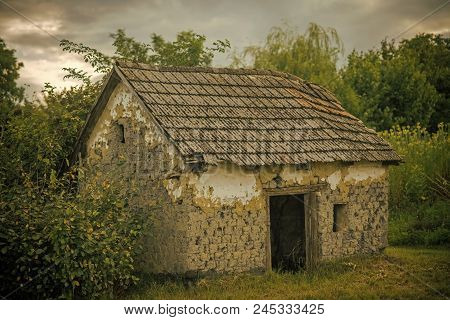 abandoned barn. Decay, decline, ruins. Village with abandoned building. House barrack in yard on natural landscape. Rural lifestyle, countryside. Architecture structure construction stock photo