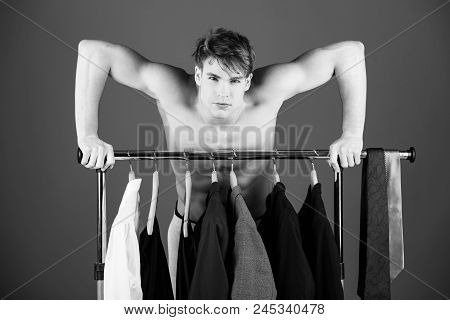 men's clothing. shaved man with naked muscular torso standing at wardrobe hanger with formal outfit of jacket, tie, shirt and suit on blue background stock photo