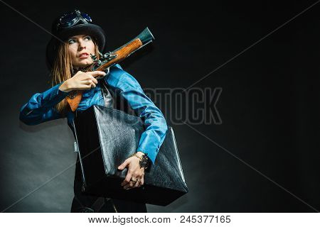 Weapon victorian style vintage concept. Subculture girl in outfit. Steam punk lady with blunderbuss and briefcase aiming for threat. stock photo