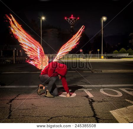 Fallen male angel kneeling in city parking lot, with fire wings spreading from his back. Unrecognizable young man stock photo