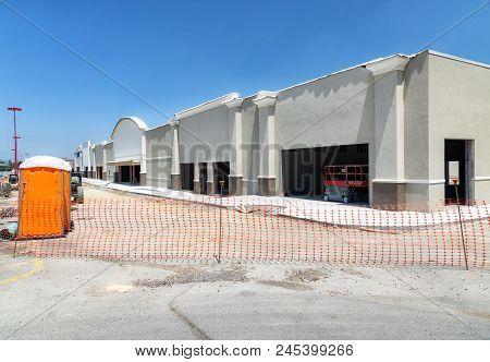 Horizontal shot from the corner of a new retail construction site in Tennessee.  It is fenced off by orange netting.  Porta potty to the side. stock photo
