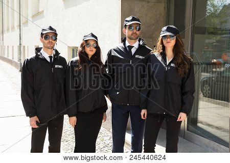 Portrait Of Young Male And Female Security Guards Wearing Uniform And Eyeglasses stock photo