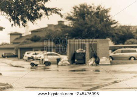 Blurred worker man collects garbage of overflowing dumpster at apartment building in Humble, Texas, US. Overfilled, on ground full of household waste, plastic bag, boxes after holidays. Vintage tone. stock photo