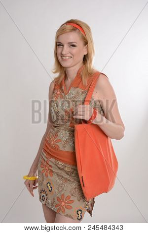 A beautiful girl posing on a gray background, an orange canvas bag in her hands. Warm colors, an orange hoop on her head, clothes from the 1970s. She is dressed in a dress with orange accents. stock photo