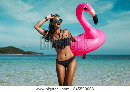 A Beautiful Sexy Amazing Young Woman On The Beach Sits On An Inflatable Pink Flamingo And Laughs, Ha