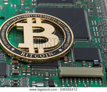 Close-up of gold bit coin, computer circuit board with bitcoin processor and microchips. Electronic currency, internet finance rypto currency. Bitcoin mining. stock photo