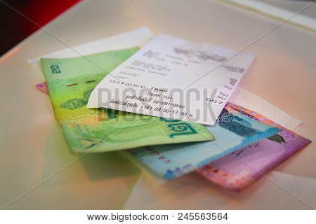 National Currency Of Thailand Baht With A Cash Check Lying On The