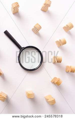 A magnifying glass lies in the center of the wooden figures of people who look at it. The concept of the search for workers and specialists, the search for a second half on a dating site. Headhunter. stock photo